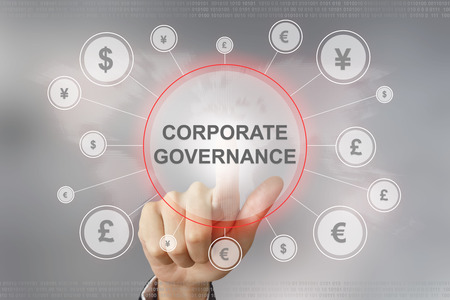 corporate governance: hand pushing corporate governance button with global networking concept