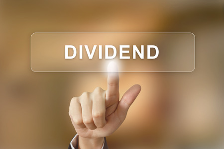 capital gains: business hand pushing dividend button on blurred background