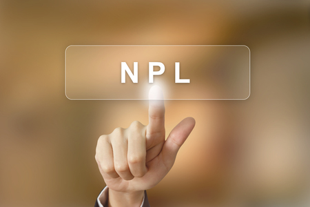 business hand pushing NPL or non performing loans button on blurred background Archivio Fotografico