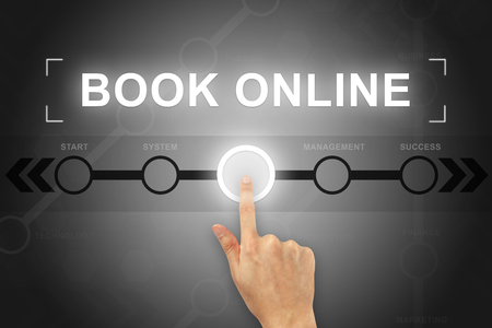 hand clicking book online button on a touch screen Banco de Imagens