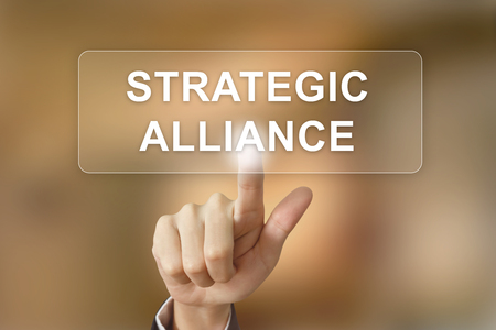 alliance: business hand pushing strategic alliance button on blurred background Stock Photo