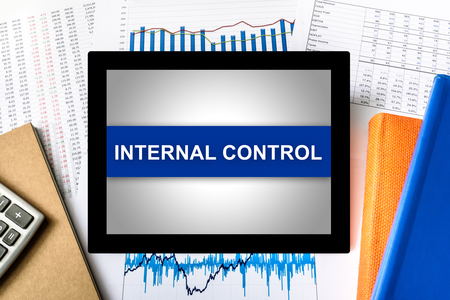 financial audit: internal control word on tablet with financial graph background