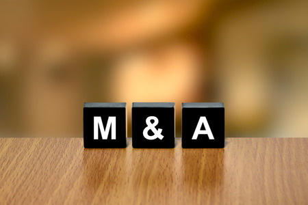 black block: M&A or merger and acquisition on black block with blurred background