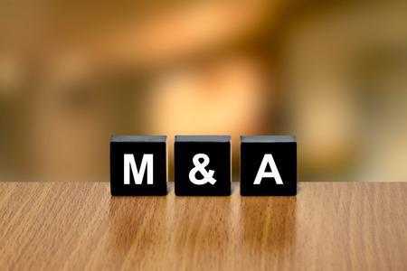 black block: M & A o de fusiones y adquisiciones en el bloque negro con fondo borroso
