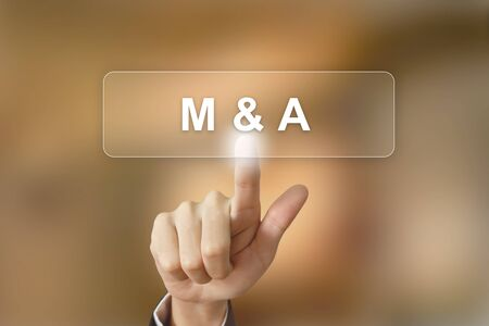 merger: business hand pushing merger and acquisition button on blurred background
