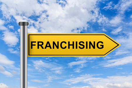 franchising: franchising words on yellow road sign on blue sky