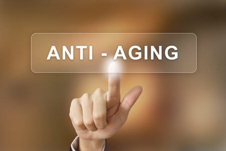 aging: business hand pushing anti aging button on blurred background