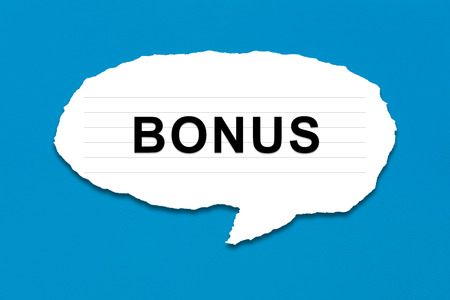 additional compensation: bonus with white paper tears on blue texture background Stock Photo
