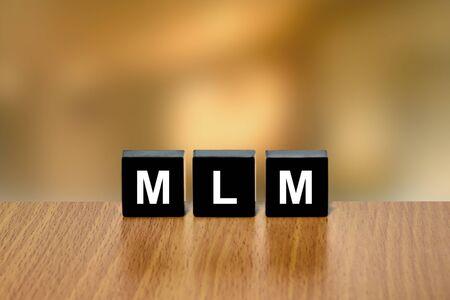black block: MLM o Multi Level Marketing en el bloque negro con fondo borroso Foto de archivo