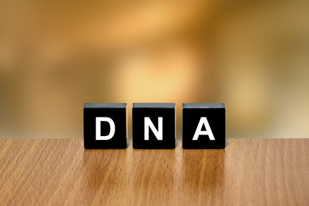deoxyribonucleic: DNA or Deoxyribonucleic Acid on black block with blurred background