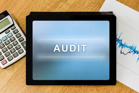 audit: audit word on digital tablet with calculator and financial graph Stock Photo