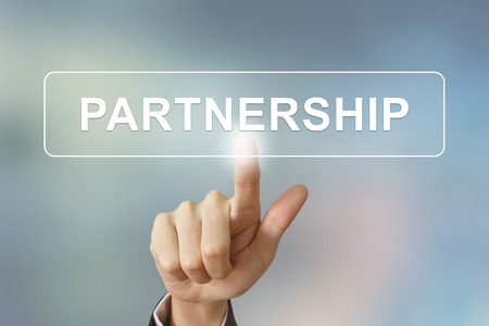 alliances: business hand pushing partnership button on blurred background Stock Photo