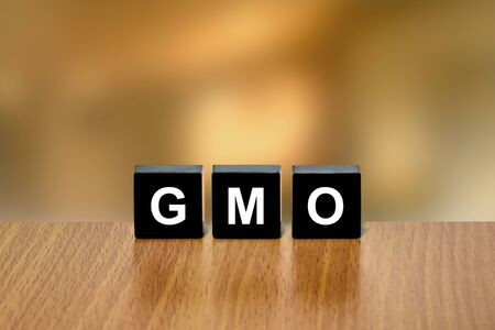 genetically: GMO or Genetically Modified Organism on black block with blurred background