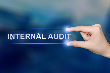 hand pushing internal audit button on blurred blue background Archivio Fotografico