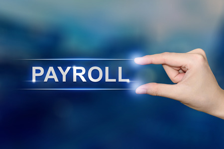 hand pushing payroll button on blurred blue background