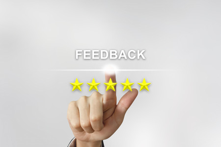 five stars: business hand clicking feedback with five stars on screen Stock Photo