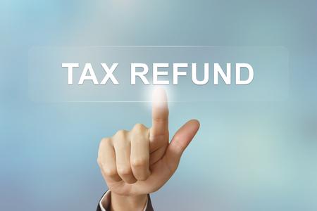 tax refund: business hand pushing tax refund button on blurred background