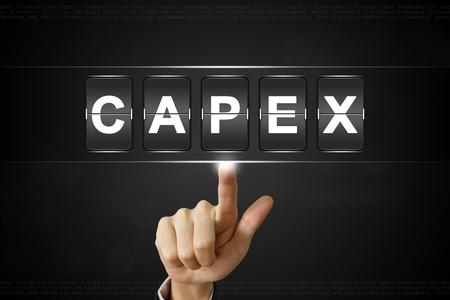 expenditure: business hand pushing capex or Capital expenditure on Flipboard Display