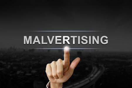 business hand clicking malvertising button on black blurred background