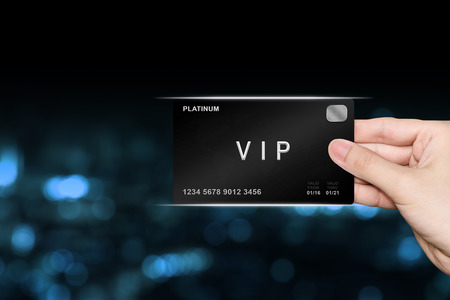 hand picking VIP or very important person platinum card on blur background Stock Photo