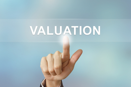 valuation: business hand pushing valuation button on blurred background