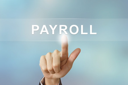 bank records: business hand pushing payroll button on blurred background Stock Photo