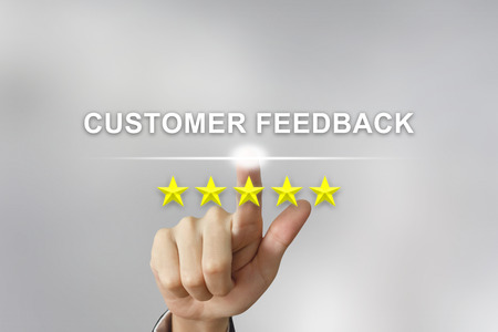business hand clicking customer feedback with five stars on screen Stok Fotoğraf
