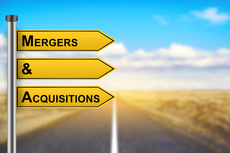 acquiring: M&A or Mergers and Acquisitions words on yellow road sign with blurred background