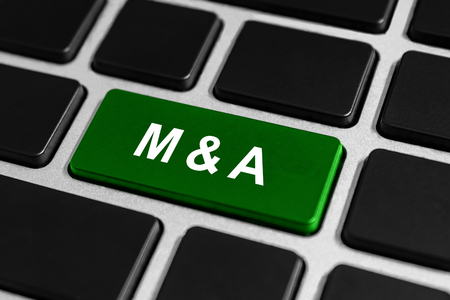 acquisitions: M&A or mergers and acquisitions green button on keyboard, business concept
