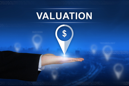 valuation: financial valuation button with business hand on blurred background Stock Photo