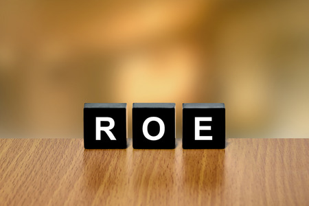 equity: ROE or return on equity on black block with blurred background Foto de archivo