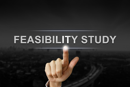 feasibility: business hand clicking feasibility study button on black blurred background