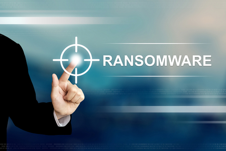 business hand pushing ransomware button on a touch screen interface