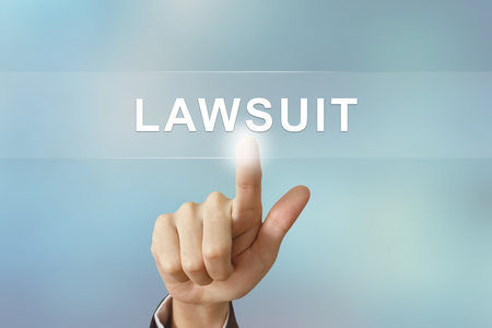 fair trial: business hand pushing lawsuit button on blurred background Stock Photo