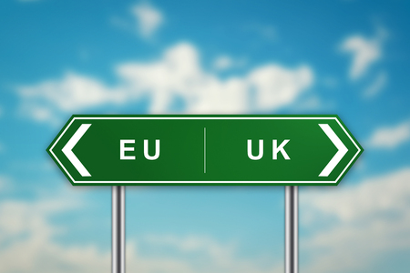 EURO and UK on green road sign with blurred blue sky, brexit or british exit concept Stock Photo
