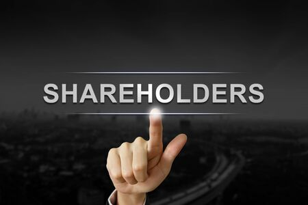 shareholders: business hand clicking shareholders button on black blurred background