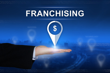 franchising: franchising button with business hand on blurred background Stock Photo
