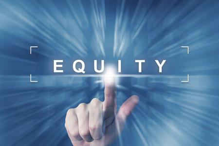 equidad: mano haciendo clic en el bot�n de la equidad con efecto zoom de fondo Foto de archivo