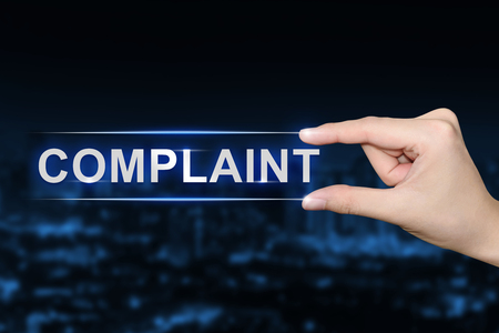 complaint: hand pushing complaint button on blurred blue background Stock Photo