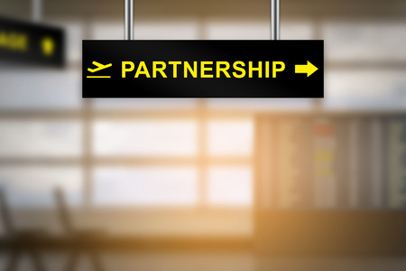 cooperate: partnership on airport sign board with blurred background and copy space