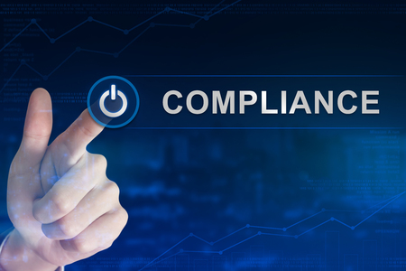 compliant: double exposure business hand clicking compliance button with blurred background Stock Photo