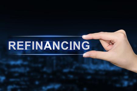 Hand drücken Refinanzierung Taste auf blauem Hintergrund unscharf