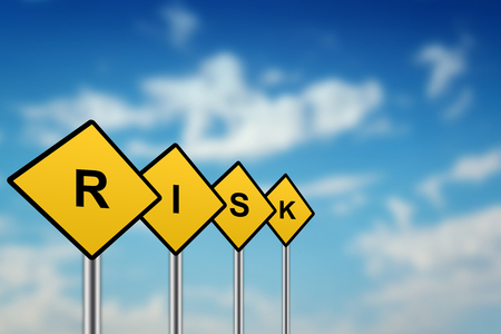 reduce risk: risk on yellow road sign with blurred sky background