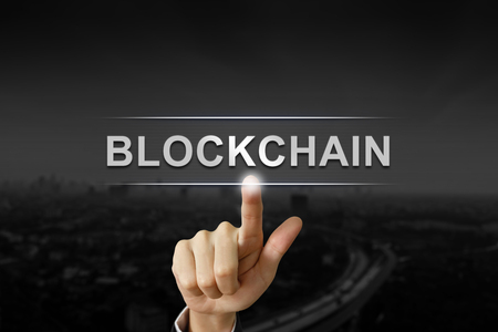 business hand clicking blockchain button on black blurred background