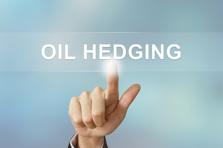 hedging: business hand pushing oil hedging button on blurred background