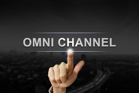 business hand clicking omni channel button on black blurred background Archivio Fotografico