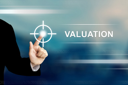valuation: business hand pushing valuation button on a touch screen interface