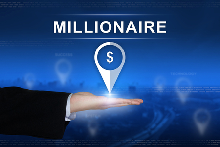 millonario: millionaire button with business hand on blurred background