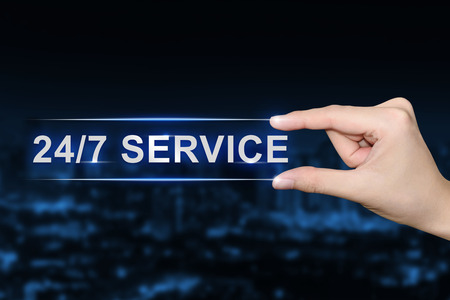 24x7: hand pushing 24 hours a day, 7 days a week service button on blurred blue background