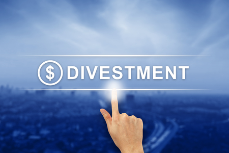 hand pushing divestment button on a virtual screen interface
